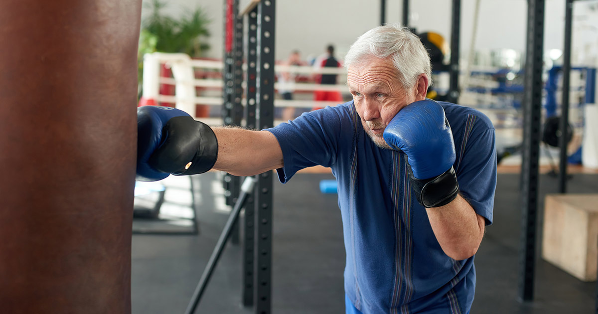 rock steady boxing man hits heavy bag